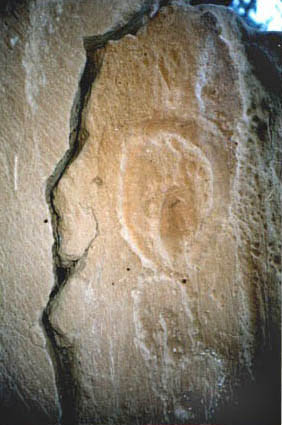 row of vulvas deeply engraved into rock wall