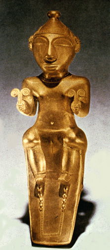 gold statue of seated goddess holding double spirals