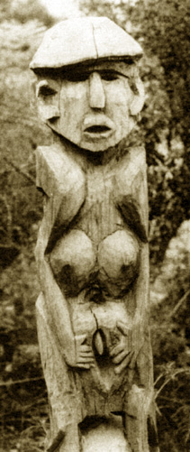 wooden statue of woman grasping her vulva