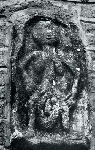 stone relief of woman holding huge vulva, on church wall